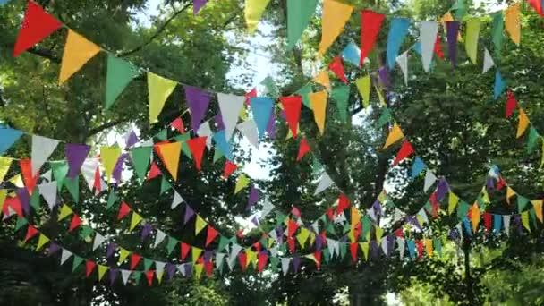 Ünnepi koszorú többszínű papír zászlók az ünnep. Tájkép egy gyerekzsúrra. Természeti dekoráció a fák hátterében. Bunting banner - színes zászlók A lapok.