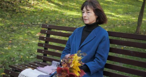 Senior woman sits on a bench in the fall in the central park of the city. The husband brings his wife a cup of hot tea to keep warm in windy weather. Leisure in the fresh air in slow motion.