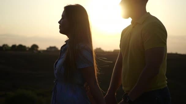 Milující dívka v šatech a chlap se drží za ruce a flirtovat ve zpomaleném filmu během západu slunce na hřišti. Šťastný a krásný vztah mladých lidí. Datum na hřišti mladého páru, detailní záběr.