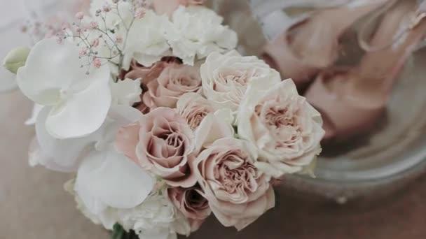 Elegantní svatební kytice květin stojí ve váze na stole. Krásné růžové a bílé růže jsou připraveny na svatbu. Detailní záběr na květiny a růžové boty ve skleněné podobě. Krajina pro svatbu
