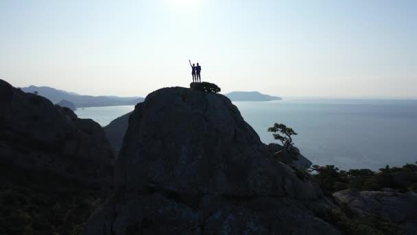 Dva mladí lidé muž a žena vyšplhali na vysokou horu a užívali si krásného obzoru Černého moře a oblohy. Dva mladí turisté dobyli horu, pohled shora ze strany.