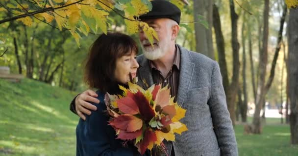 An elderly and happy couple are smiling and hugging in warm weather in a cozy autumn city park. Senior woman with leaves and man enjoy spending time outdoors among the trees. Leisure after retirement.