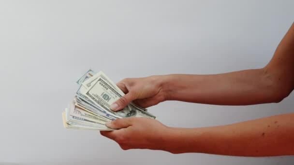 Female hands hold a wad of money and redefine them, close view on white background. Focus on womens hands, in which there are a lot of notes for 100 dollars and 50 euros. Girl recounts cash savings.