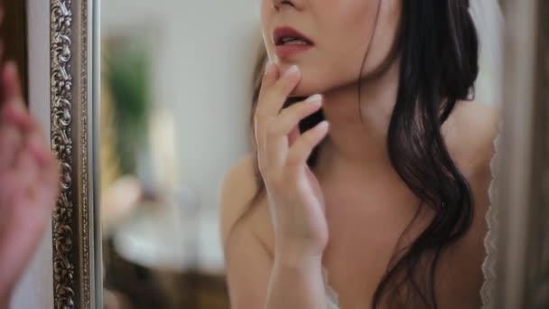 Schöne süße europäische Brünette in Make-up gekleidet in weißen sexy Spitzenunterwäsche schaut morgens in den Spiegel und bewundert ihr Gesicht und ihr tastendes Kinn. Braut mit weißer Maniküre bereitet sich auf Hochzeit vor