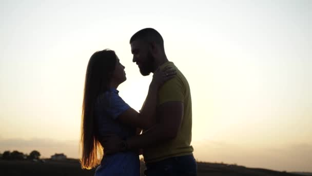 Romantic evening for two lovers standing on a deserted field against the backdrop of a beautiful dawn and meadow. A nice girl kisses and hugs her beloved under the bright sun in nature. Loving couple.