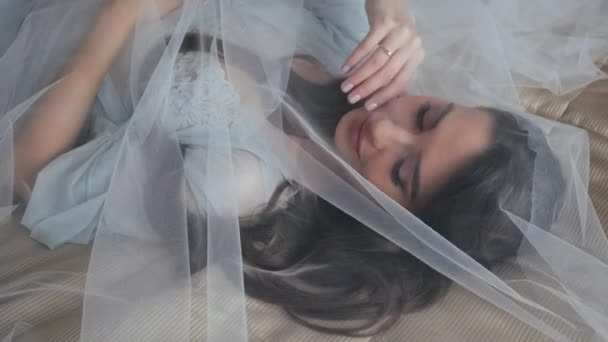 Close-up top shot of beautiful bride in sexy turquoise lingerie, which lies on a cozy bed in an expensive hotel room under a veil in the morning. Pretty woman with long hair is covered by a veil.
