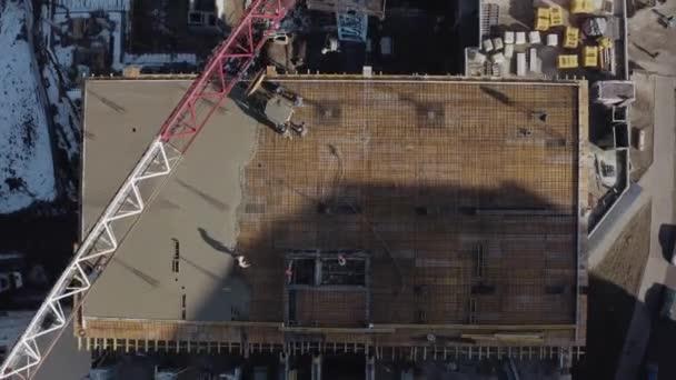 Luftaufnahmen eines Hochhauses unter einem Büro auf einer Baustelle in Charkow, Ukraine. Blick von oben auf einen Kran und Arbeiter beim Bau eines Wohnhauses. Der Bau eines neuen modernen Hauses.