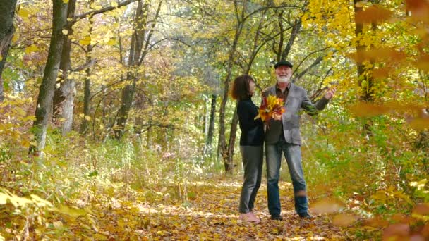 Happy cheerful elderly couple bearded husband and wife with a bouquet of leaves laughing, enjoying a walk and spending time together in a cozy autumn forest among the trees. Senior man rolls leaves.