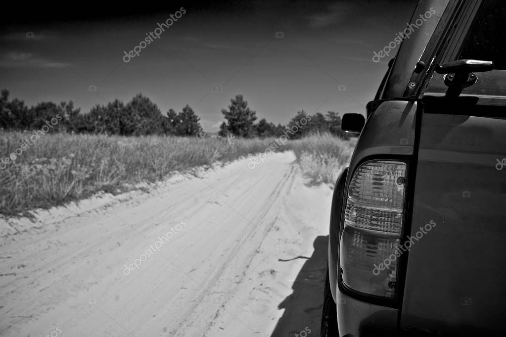 Road trip. Black and white. Pickup truck parked on the side of a dirt road. Grass and trees seen in background.