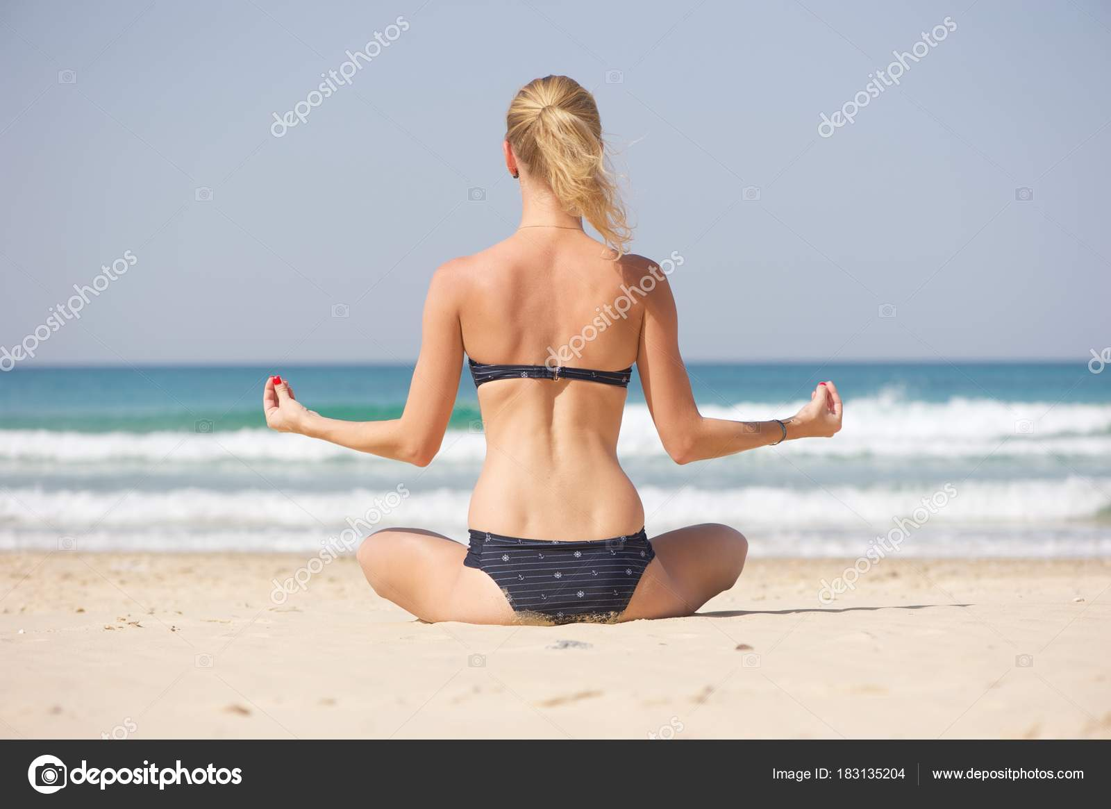 A blonde woman facing away from the camera doing yoga on a beach in a a  bikini. Beautiful sea in the background.– stock image