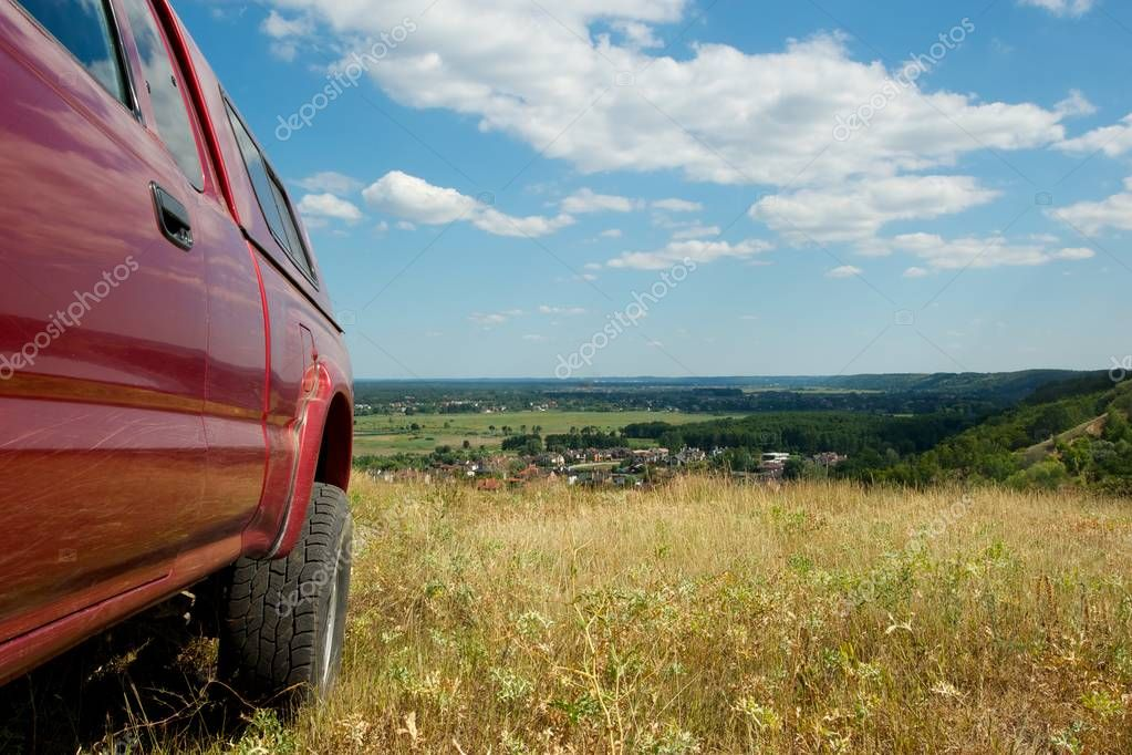 Picture taken from behind a rear wheel of a red pickup truck. Beautiful view from a mountain top. Dry grass, cloudy sky.