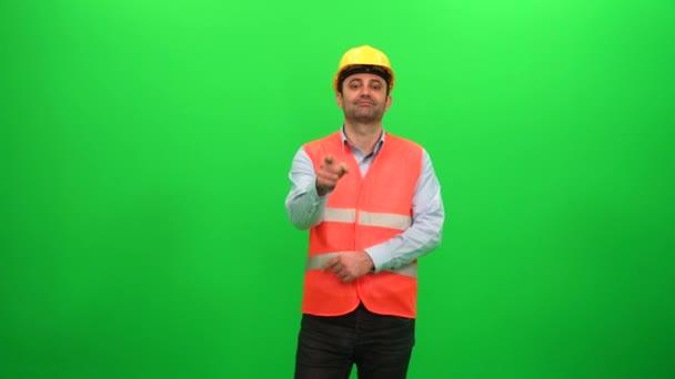 Stavební dělník body prstem na kameru