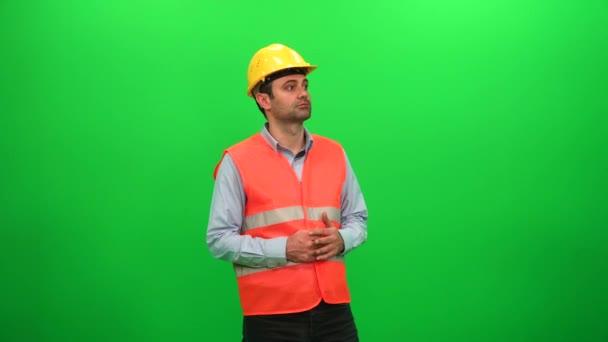 Inženýr muž rozhlížel zkoumání stavební činnost na zeleném pozadí