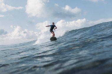 Sportsman riding wave on surf board in ocean stock vector