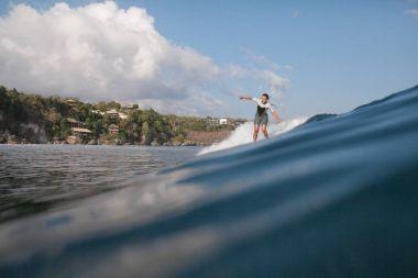 sportswoman riding wave on surf board in ocean