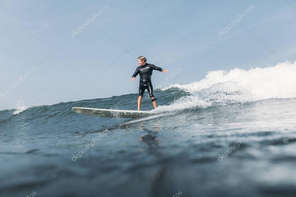 surfer having fun and riding wave on surf board in ocean