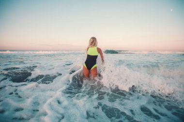 Back view of sportswoman surfing on surf board in ocean stock vector