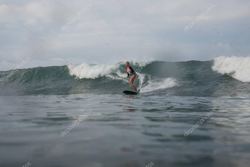 girl riding wave on surf board in ocean