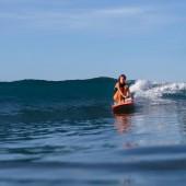 Fotografie junge schlanke Mädchen Surfen im Ozean