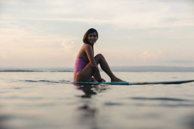 beautiful girl sitting on surfboard in water in ocean at sunset