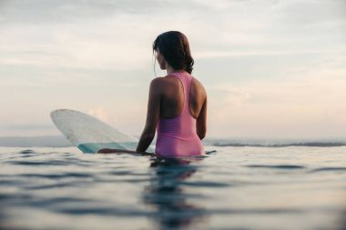 back view of girl sitting on surfboard in ocean at sunset