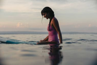 sporty girl sitting on surfboard in water in ocean at sunset