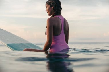 beautiful woman sitting on surfboard in ocean at sunset