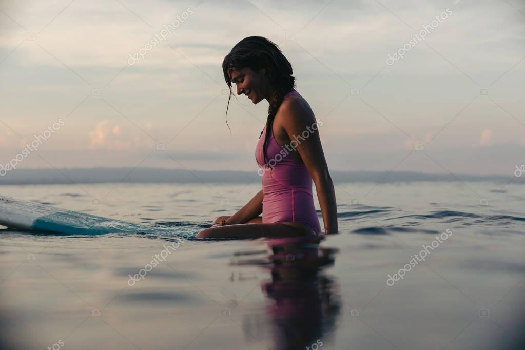 Фотообои sporty girl sitting on surfboard in water in ocean at sunset