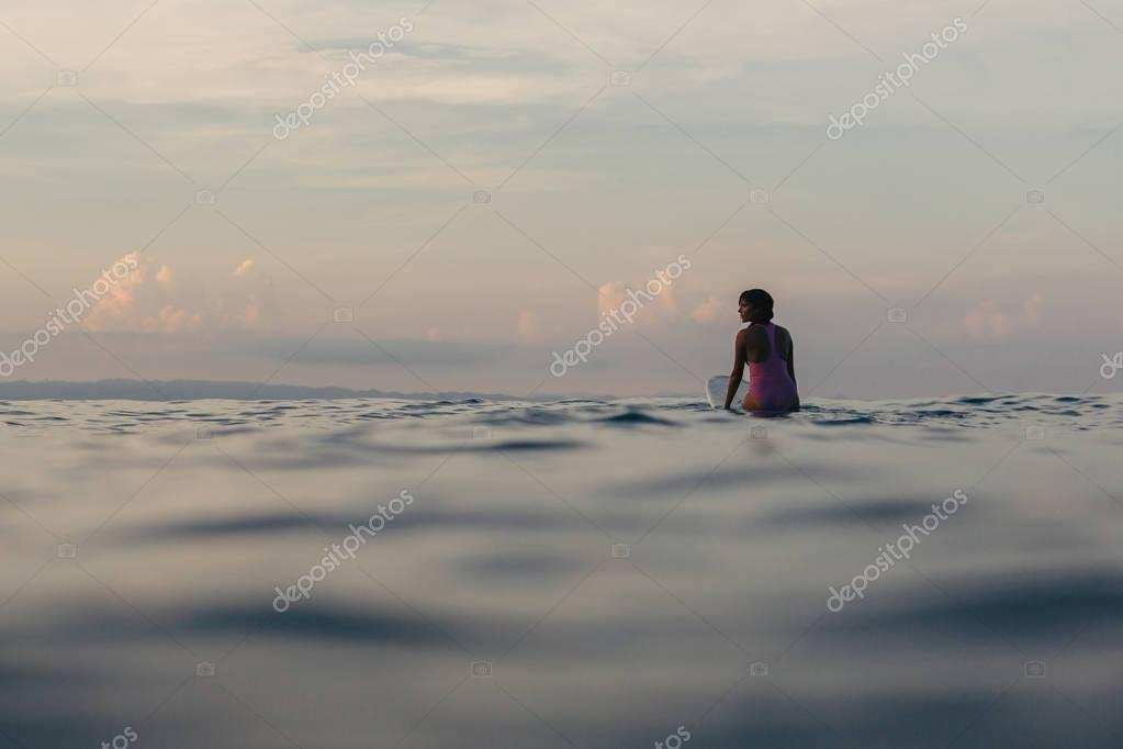 Фотообои silhouette of surfer sitting on surfboard in water at sunset