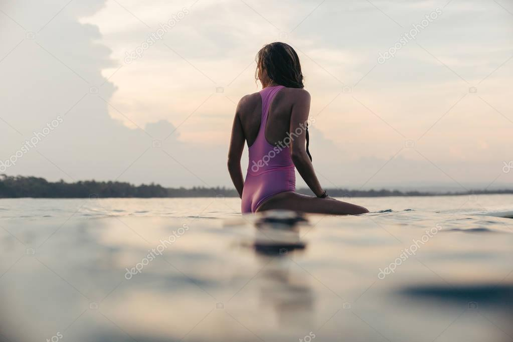 Фотообои silhouette of surfer in pink swimsuit sitting on surfboard at sunset