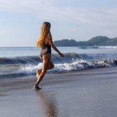 mladá žena běží na tropické pláži u oceánu