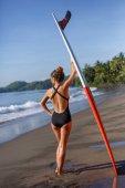 Rückansicht des jungen weiblichen Surfer am Strand mit roten und weißen Surfbrett stehend