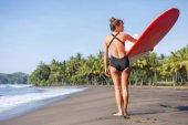 zadní pohled na mladou dívku drží červené surfu na pláži