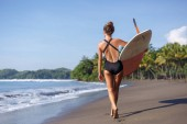 back view of young surfer walking with surfboard on beach
