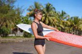 young woman in black swimsuit holding surfboard on beach