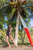 Fényképek vonzó fiatal lány tánc közelében palm szörfdeszka fürdőruha