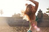 Fotografie boční pohled na krásná mladá žena v bikinách, hrát si s vlasy pomocí slunečního světla na pozadí