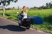 Fotografie rear view of woman riding scooter with surfing board