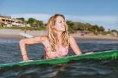 Fotografie portrét mladé ženy v plavání oblek s surfování desky v oceánu