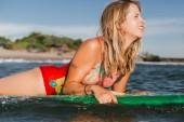 Fotografie portrét mladé ženy v plavání oblek na desce surfing v oceánu