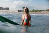 portrét ženy v plavkách, spočívající na desce surfování v oceánu s pláží na pozadí