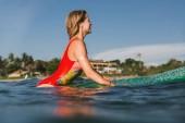 boční pohled na ženy v plavkách na desce surfování v oceánu