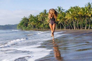back view of woman running on tropical beach near ocean