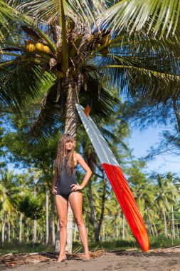 young slim woman posing with red surfboard near palm tree