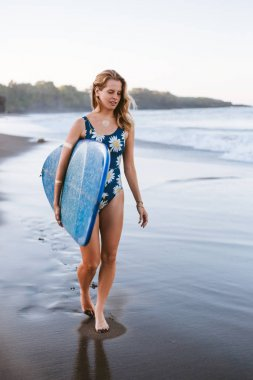 young sportswoman in swimming suit with blue surfing board walking on coastline