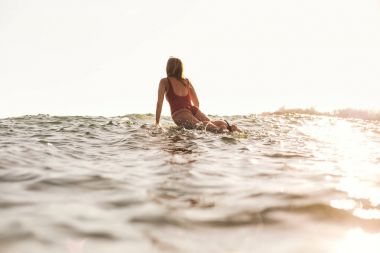 back view of woman in swimming suit surfing in ocean