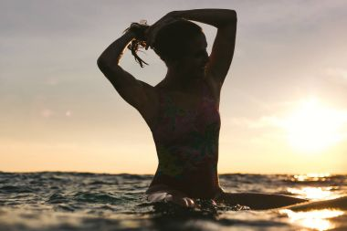 silhouette of woman readjusting hair while sitting on surfing board in ocean on sunset