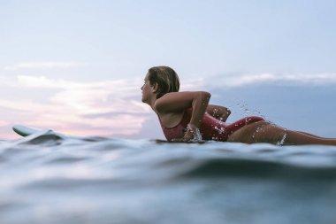 side view of sportswoman in swimming suit surfing alone in ocean