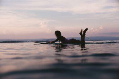 Silhouette of sportswoman lying on surfing board in ocean on sunset stock vector