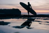 Fotografia silhouette of young woman with surfboard on seashore in evening